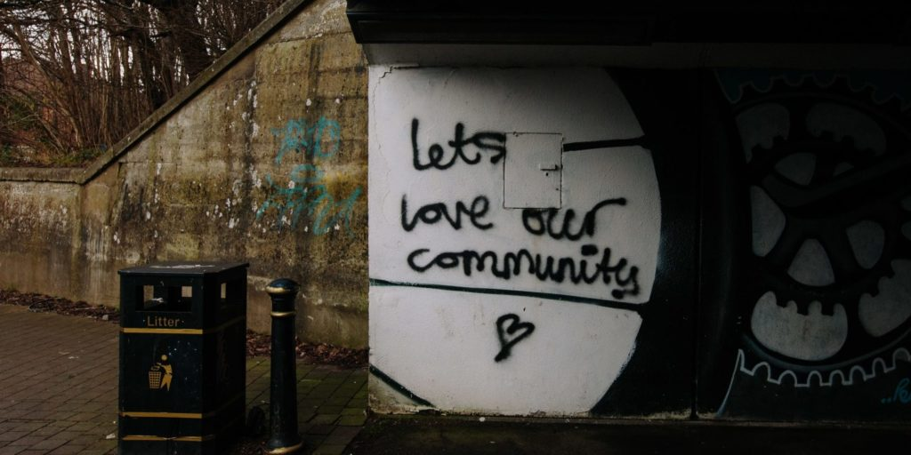 """underpass sign that says """"Let's Love Our Community"""""""